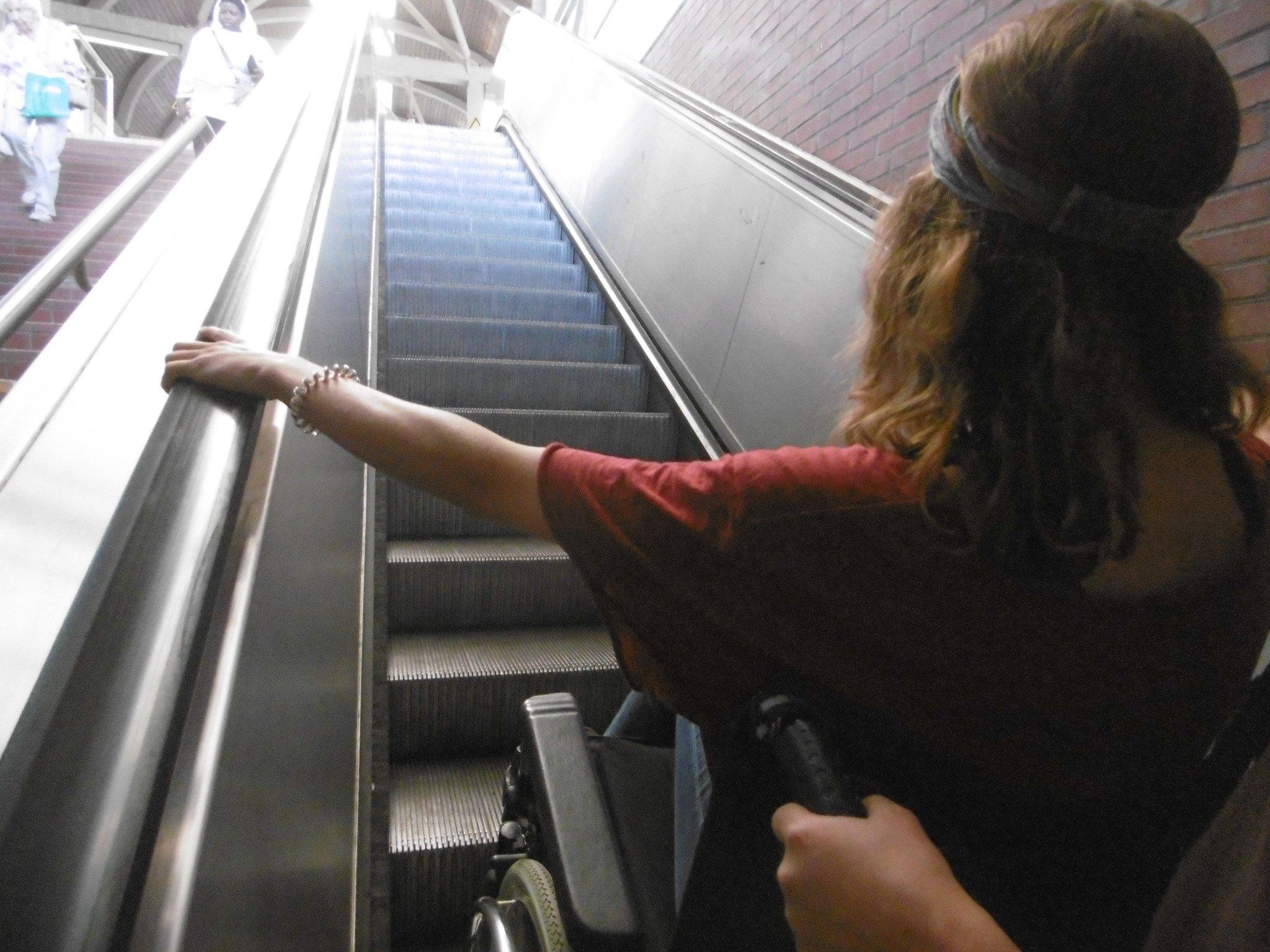 Eine Frau im Rollstuhl auf einer Rolltreppe