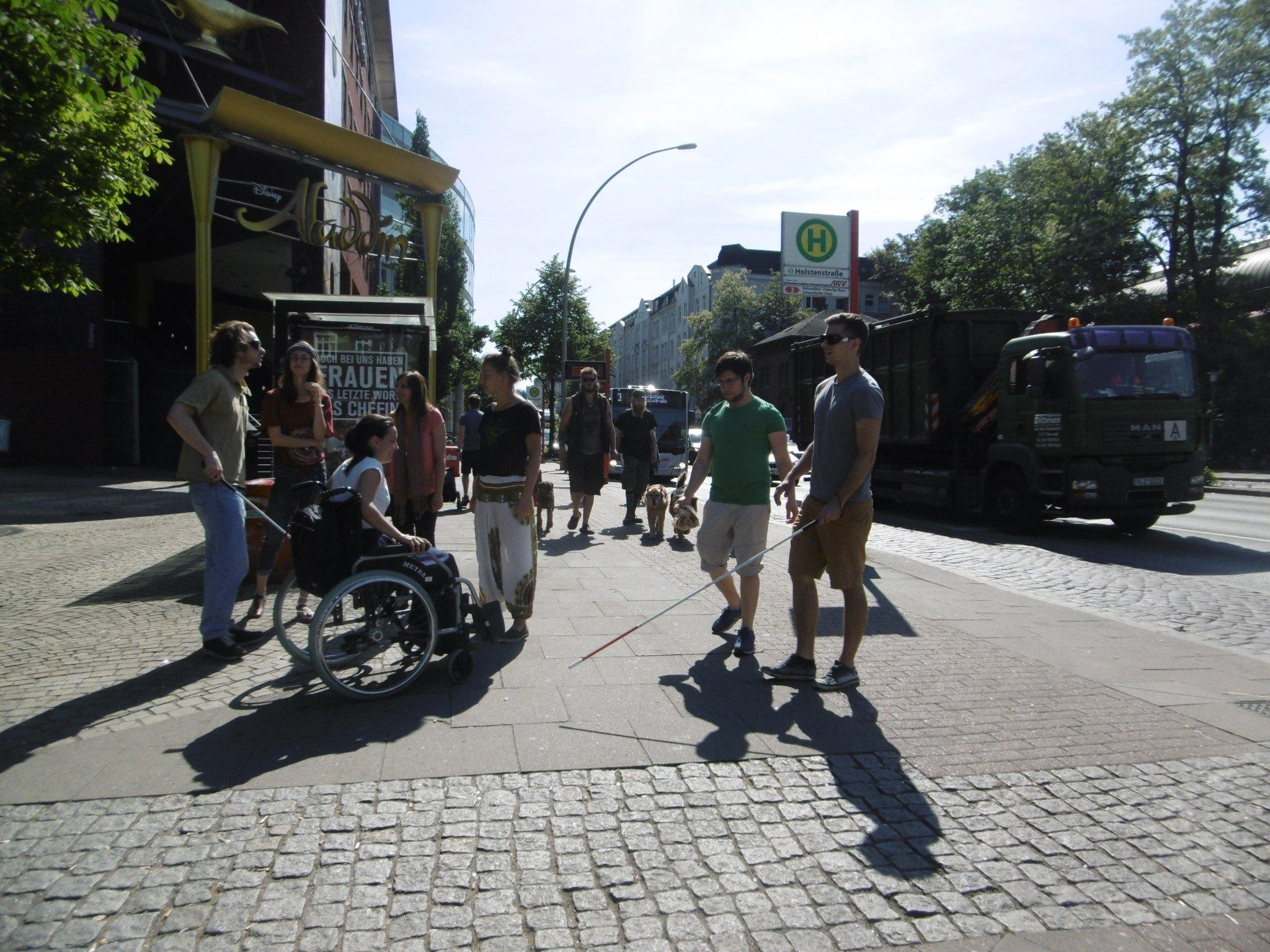 Seminarteilnehmer im Rollstuhl und mit Taststöcken im Straßenverkehr